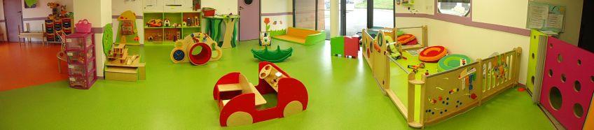 La photographie montre la salle de jeux, à dominante verts. Deux expaces distincts : un petit parc pour les bébés est inclus dans la salle des plus grands.